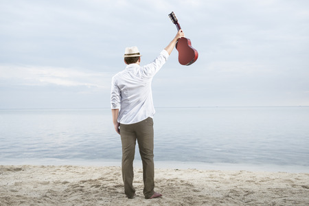 Rear view of asian businessman in hat and white clothes holding guitar on the beach. Summer vacation Stockfoto