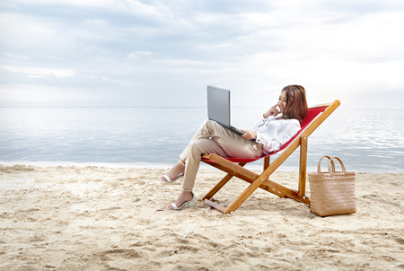 Asian business woman working with laptop sitting in the beach chair on beach. Summer vacation