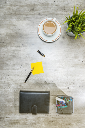 Top view of business desk with coffee, potted plant, notebook, notes paper and business accessories on the office Stockfoto