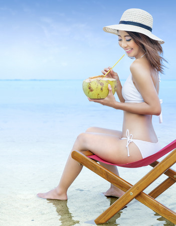 Asian sexy girl in bikini and hat with coconut fruit while sitting on the beach chair at seaside. Summer vacation