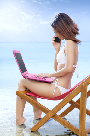 Asian sexy girl in bikini with laptop talking on the mobile phone on the beach chair at seaside. Summer vacation Stockfoto
