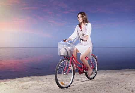 Asian sexy girl riding a bicycle on the beach at sunset. Summer vacation