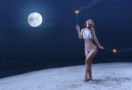 Asian sexy girl in bikini holding fireworks on the beach at night. Summer vacation