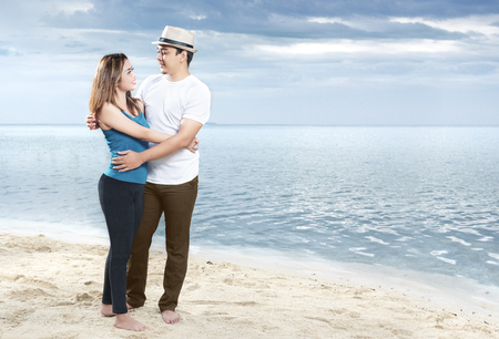 Happy asian man in hat hugging his girlfriend on the beach. Summer vacation