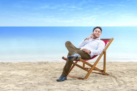 Asian businessman talking on mobile phone while lean back in the beach chair on beach. Summer vacation