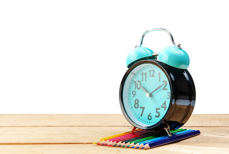 Alarm clock and colored pencils on wooden table isolated over white background. Back to School concept Stockfoto