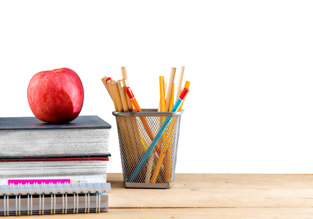 Pile of books with apple and pencils in basket container on wooden table isolated over white background. Back to School concept