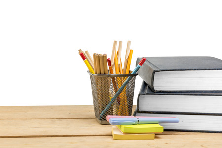 Pile of books with notes paper and pen with pencils in basket container on wooden table isolated over white background. Back to School concept