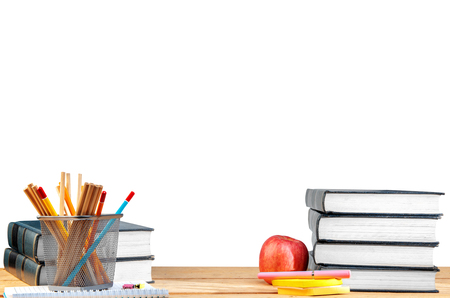 Pile of books with notes paper and pen, apple and pencils in basket container on wooden table isolated over white background. Back to School concept 免版税图像