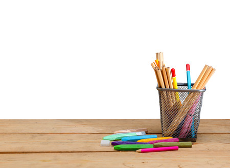 Pencils in basket container and colorful crayons on wooden table isolated over white background. Back to School concept Stockfoto