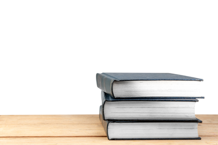 Pile of books on wooden table isolated over white background. Back to School concept
