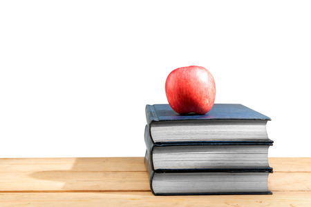 Pile of books with apple on wooden table isolated over white background. Back to School concept Stockfoto