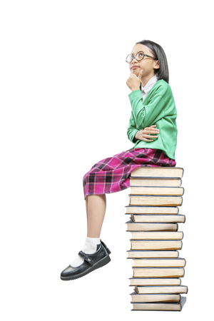 Asian cute girl with glasses think while sitting on the pile of books isolated over white background. Back to School concept