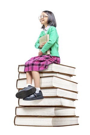 Asian cute girl with glasses holding the book while sitting on the pile of books isolated over white background. Back to School concept Stockfoto