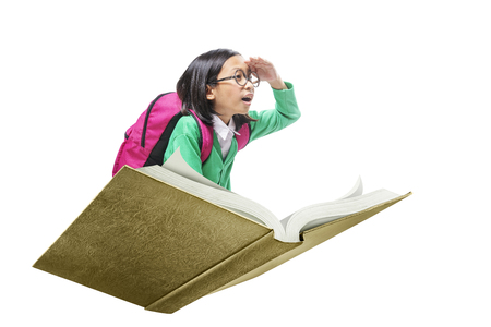 Asian cute girl with glasses and backpack sitting on book isolated over white background. Back to School concept