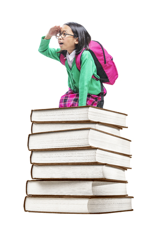 Asian cute girl with glasses and backpack sitting on the pile of books isolated over white background. Back to School concept