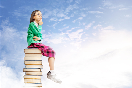 Asian cute girl with glasses think while sitting on the pile of books with blue sky background. Back to School concept
