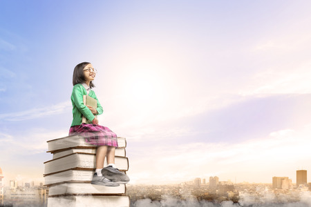 Asian cute girl with glasses holding the book while sitting on the pile of books with city and blue sky background. Back to School concept
