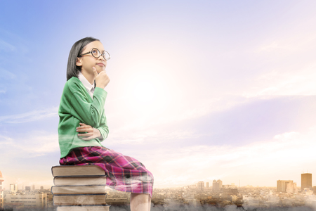 Asian cute girl with glasses think while sitting on the pile of books with city and blue sky background. Back to School concept