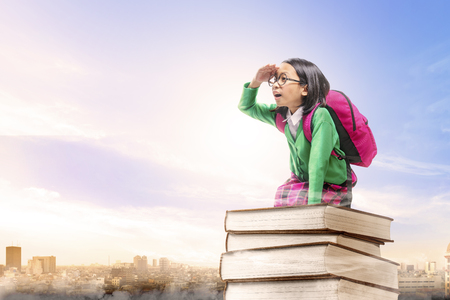Asian cute girl with glasses and backpack sitting on the pile of books with city and blue sky background. Back to School concept