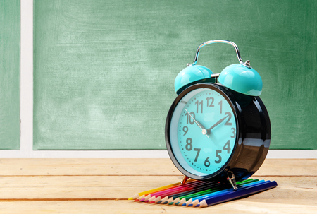 Alarm clock and colored pencils on wooden table with chalkboard background. Back to School concept