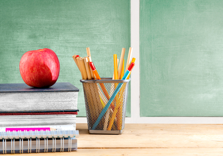 Pile of books with apple and pencils in basket container on wooden table with chalkboard background. Back to School concept