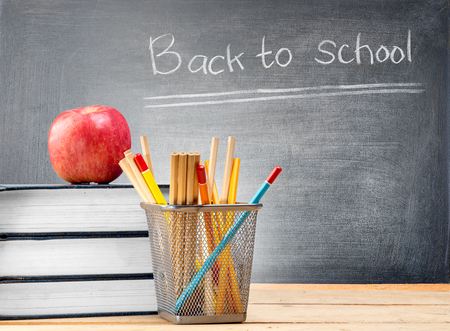Pile of books with apple and pencils in basket container on wooden table and blackboard with Back to School message. Back to School concept Stockfoto