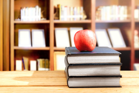 Pile of books with apple on the wooden table in library. Back to School concept Stockfoto