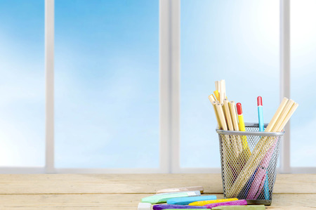 Pencils in basket container and colorful crayons on the wooden table. Back to School concept