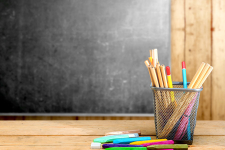 Pencils in basket container and colorful crayons on the wooden table with blackboard background. Back to School concept