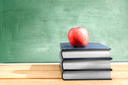 Pile of books with apple on the wooden table with chalkboard background. Back to School concept Stockfoto