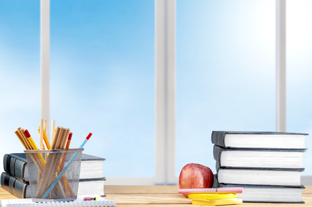 Pile of books with notes paper and pen, apple and pencils in basket container on the wooden table. Back to School concept Stockfoto