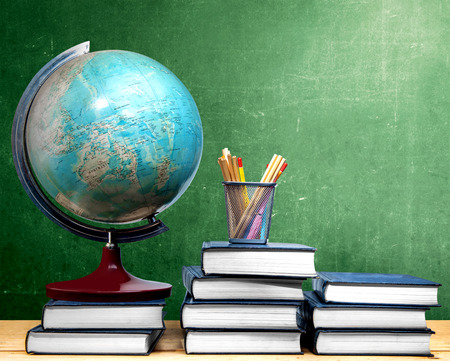 Pile of books and globe with pencils in basket container on wooden table with chalkboard background. Back to School concept