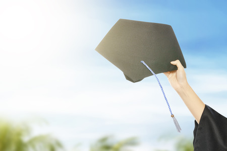Hand holding graduation hat with blue sky background. Graduation concept Stockfoto