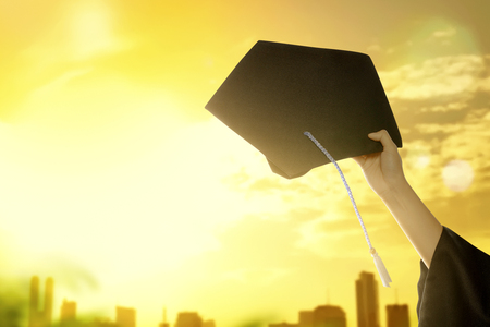 Hand holding graduation hat with sunlight background. Graduation concept