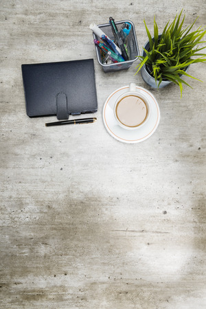 Top view of business desk with coffee, potted plant, notebook and business accessories on the office