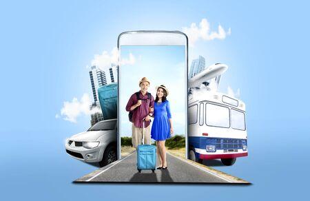 Mobiele telefoon met vervoer en gebouwen op blauwe achtergrond. Uit de telefoon komt een Aziatisch stel in hoed met koffertas en rugzak die op straat staat. Reisconcept Stockfoto