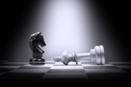 White king chess piece defeating by black knight chess piece on the chessboard
