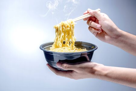 People eat the noodles with chopstick over bright background