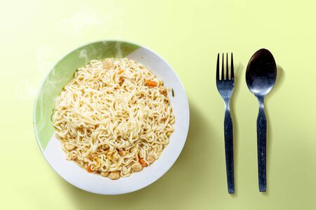 Noodles on the bowl with spoon and fork on green background