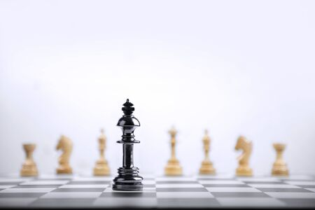 Black king chess piece standing in front of whole group of wooden chess pieces on the chessboard