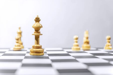 Wooden king chess piece standing on the chessboard