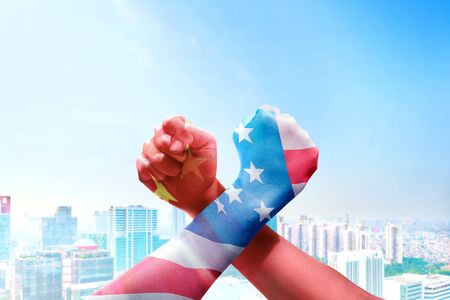 People with Chinese skin and American skin arm-wrestling over cityscapes background. Trade war Chinese against America Standard-Bild - 129159893