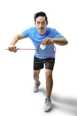 Asiatischer Mann mit Badmintonschläger hält Federball und ist bereit in Aufschlagposition isoliert auf weißem Hintergrund Standard-Bild