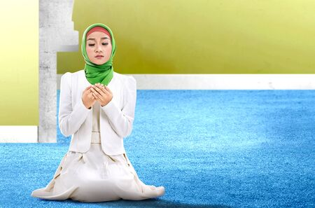 Asian Muslim woman sitting in pray position while raised hands and praying inside the mosque