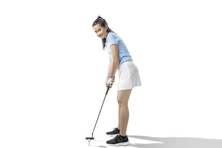 Asian woman with a putter golf club ready to hit the ball isolated over white background