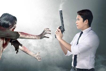 Asian businessman with the gun on his hand face the zombies amid the fog. Halloween concept
