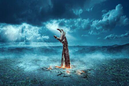 Aufstieg der Zombiehand vom Boden nachts mit Mondlicht und dunklem Wolkenhintergrund. Halloween-Konzept