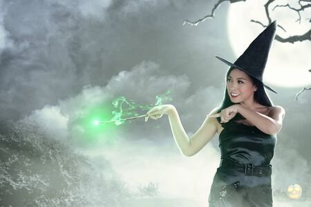 Asian witch woman using the wand with magic shine with moonlight background. Halloween concept Stock Photo