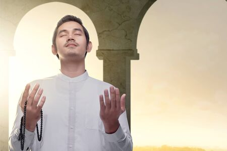 Asian Muslim man standing and praying with prayer beads while raised arms inside the mosque